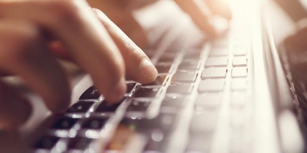 Une main en train de taper sur un clavier d'ordinateur