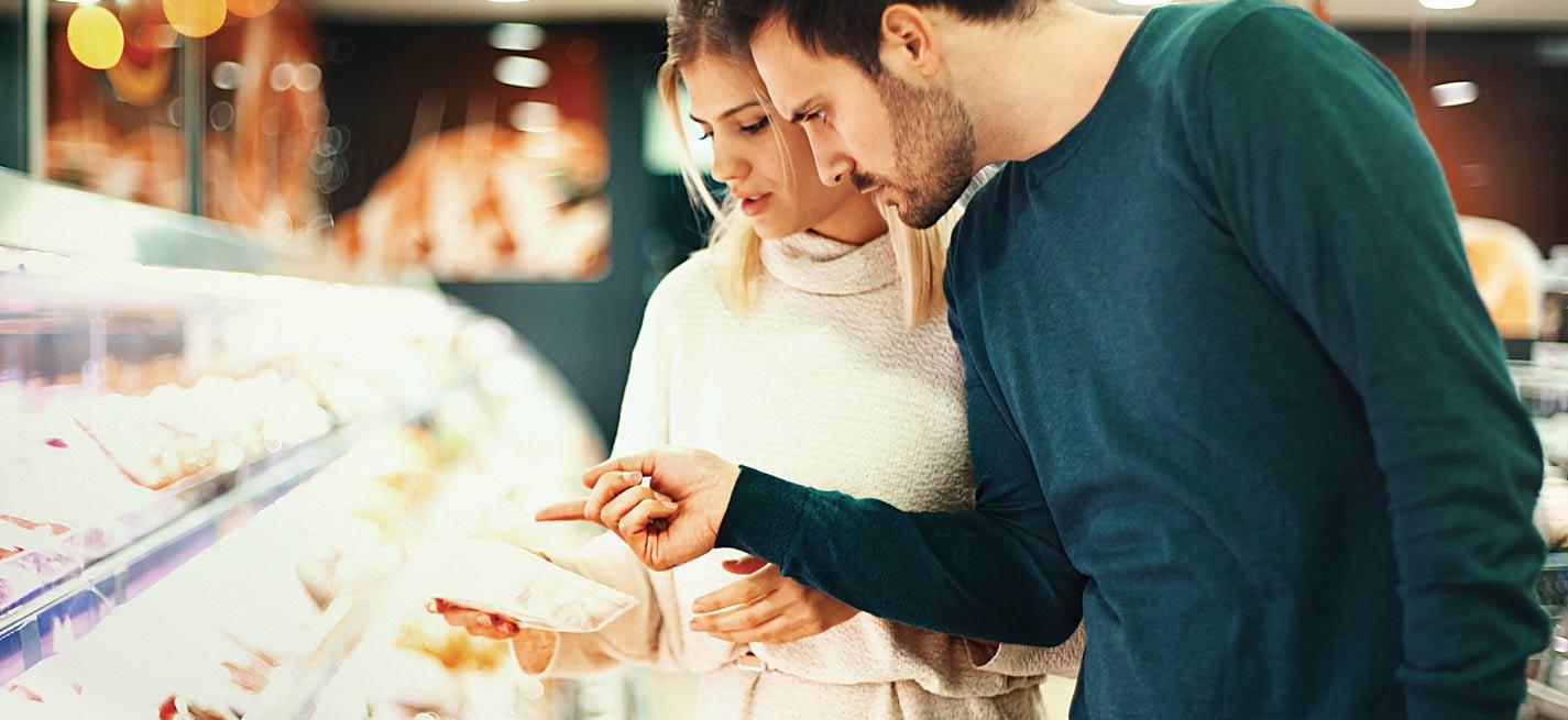 Couple devant un rayon de viande dans un supermarché
