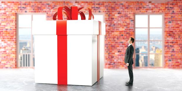 Une personne devant un énorme paquet cadeau